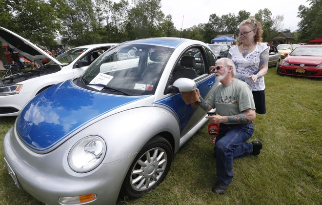 """Ken and Leah Corey of Bath polish their custom-painted 2005 Volkswagen Beetle at Bugfest. Though Ken said that he does not usually name the 23 bugs he's owned throughout his life, he named the silver and blue metallic car – the """"youngest"""" car in his collection – Belle, from """"Beauty and the Beast."""""""