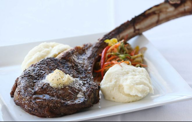 The 32-ounce Tomahawk Bone-In Ribeye Steak from Lucia's on the Lake is topped with garlic-herb butter, served with mashed potatoes and fresh vegetables.  (Sharon Cantillon/Buffalo News)