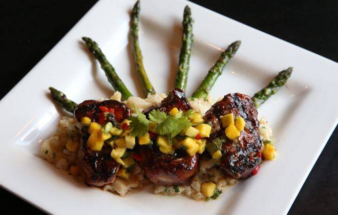 Pork is glazed with honey chipotle barbecue sauce and topped with mango salsa. It's served with New York apple risotto and grilled asparagus. (Sharon Cantillon/Buffalo News)