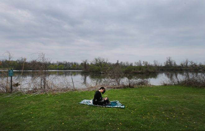 Katy Walsh does some writing on a blanket in South Park in South Buffalo.  (Mark Mulville/Buffalo News)