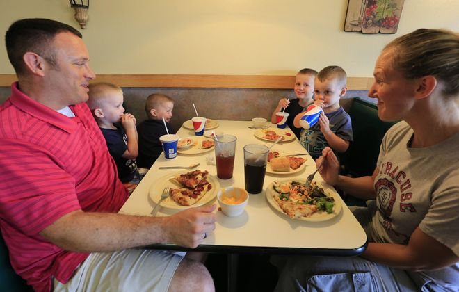 """Patrick Eustace sits next to his sons, Andrew, 3, Ethan, 3, and his wife Amy sits next to Dillon, 3, and Gavin, 4, at Toni Pepperoni's buffet in Orchard Park.  """"'Big families are like water bed stores: they used to be everywhere, and now they're just weird.'"""" Larry Muscoreil, quoting comedian Jim Gaffigan"""