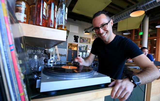 Handlebar Pub bartender Adam Rath plays vinyl records on Swan Street in downtown Buffalo. (Harry Scull Jr./Buffalo News)