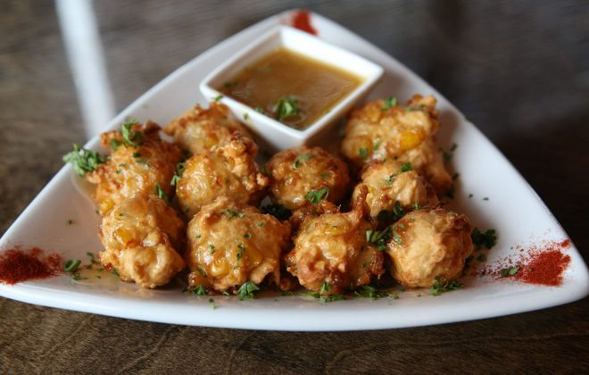 The corn fritters at the Griffon Gastropub in Clarence are spoonfuls of fresh sweet corn-filled batter, flash-fried and served with Vermont maple butter. (Sharon Cantillon/Buffalo News)