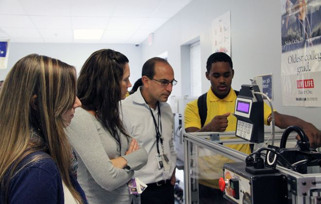 CSAT teacher Christopher Derrick (second from right) works with student Cary Jackson, right, on an iCarver in the school's advanced manufacturing lab.