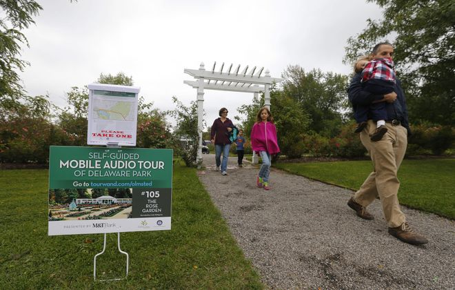 Visitors walk through the Rose Garden past a sign announcing a self-guided mobile audio tour of Delaware Park that was unveiled Tuesday. The M&T Bank-sponsored program can be accessed via smartphone or followed on printed maps.
