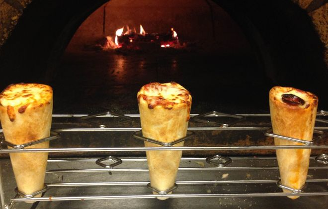 Three pizza cones emerge from the wood-fired oven Pizza Amore. (via Pizza Amore)