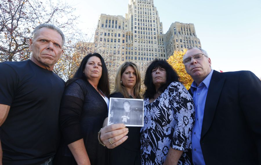 Siblings of the late Robert Runfola – from left, Louis Jr. and Cynthia Sirianni, Andrea Ryan, and Lisa and Anthony Sirianni – hold his photo at Niagara Square.