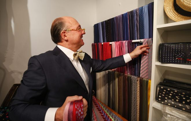 """Clothier Tom Barnett helps a customer select  a matching tie for his suit at his cozy shop in Snyder. """"If you're going to wear these clothes, you should look great,"""" he says."""