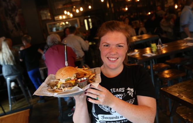 Allen Burger Venture is at 175 Allen St. in Buffalo.  Their burgers are dry-aged grass-fed angus beef burgers which are hormone and antibiotic free.  Server Sarah Francis presents the All-American burger which is topped with American cheese, shredded lettuce, tomato, onion, pickle and Triple D sauce.  Photo taken, Wednesday, Oct. 7, 2015.  (Sharon Cantillon/Buffalo News)
