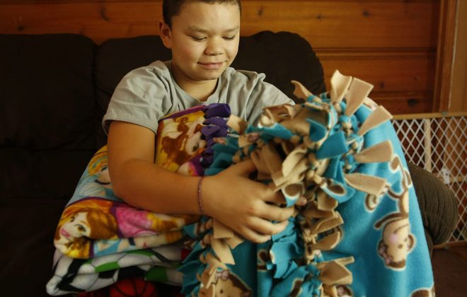 Kwentin Foster and some of the blankets he's made. (Mark Mulville/Buffalo News)