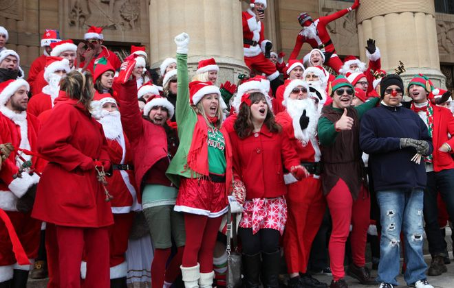 Each year, throngs of Western New Yorkers dress as Santas, elves and other holiday characters, while participating in a bar crawl and donating toys to a local boys and girls club. (Sharon Cantillon/Buffalo News file photo)