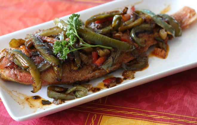 Whole fried fish topped with sliced green and red bell peppers in a piquant brown sauce from A Taste of Caribbean. (Sharon Cantillon/Buffalo News)