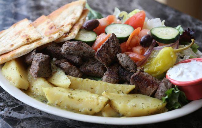 Marinated beef is served with a Greek salad, oven-roasted Greek potatoes, pita and tzatziki at Eggsperience Vasilis. (Sharon Cantillon/Buffalo News)