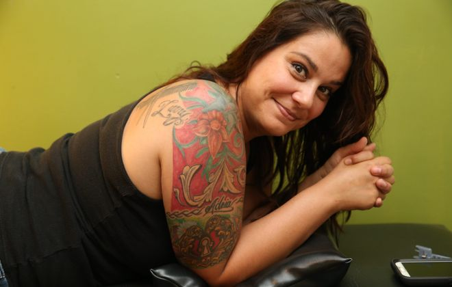 """Gina World gets a tattoo on her calf by tattoo artist Ronnie Schrimmel at Upstate Ink on Amherst Street in July 2015. Although World's art has specific meanings to her, she doesn't buy into the idea that everyone needs an emotional backstory to get a tattoo.  """"It's your art. You like it,"""" she said. (Sharon Cantillon/Buffalo News)"""