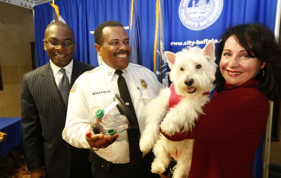 Ann Louise Ciminelli holds her dog Minnie after presenting animal oxygen masks Friday to Fire Commissioner Garnell W. Whitfield, center, and Buffalo Mayor Byron W. Brown.