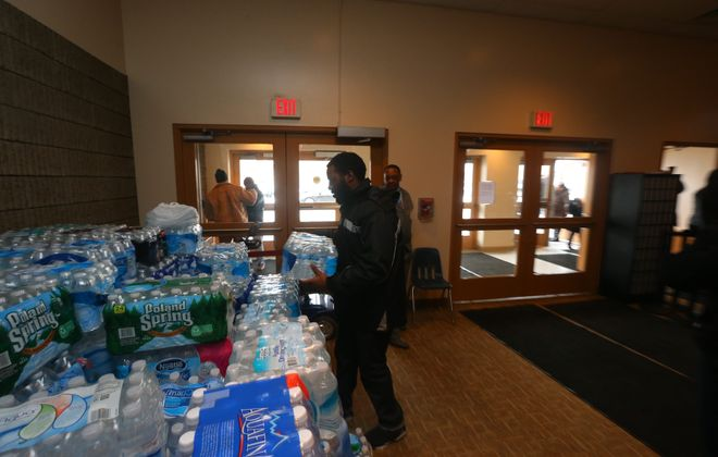 Camyr Nelson brings a case of water Sunday to First Bethel Baptist Church, where church members are collecting bottled water to send to Flint, Mich.