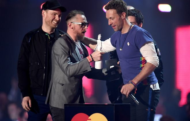 EBRUARY 24:  Chris Martin from Coldplay receives the Best British Group award from presenter Simon Pegg at the BRIT Awards 2016 at The O2 Arena in London on Wednesday.