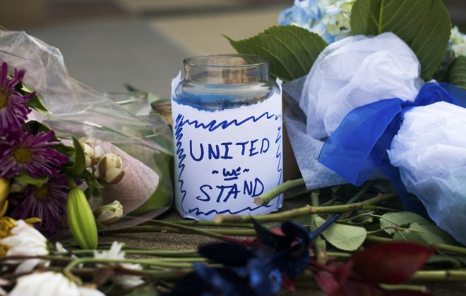 """A candle with the message """"United We Stand"""" sits amongst other mementos at a makeshift memorial set up outside Dallas Police Department headquarters, following a sniper attack that  five officers and wounded seven others at a demonstration on Thursday night against police shootings in Minnesota and Louisiana. (The New York Times)"""