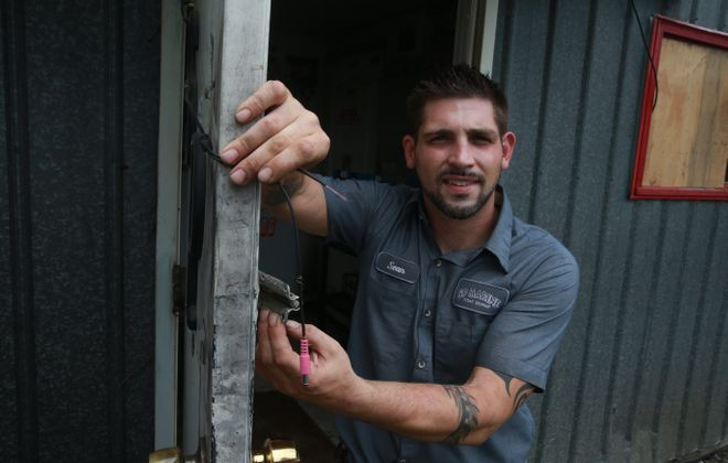 Sean Polley shows the broken deadbolt and wires from security video camera damaged in break-in over the weekend at boat repair shop SP Marine in Wheatfield.  (John Hickey/Buffalo News)
