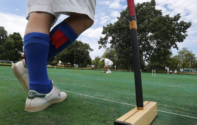 Russ Brown, center, lines up his shot while Patrick Little waits his turn during their match in the Buffalo Croquet Club's Inaugural 6-Wicket Invitational at Delaware Park in Buffalo on Saturday. Below, Ryan Thompson concentrates on his game.