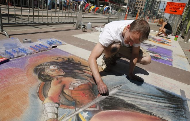Joe Mahley of Lockport draws Wonder Woman at ChalkFest Buffalo on the 500 block of Main Street, Saturday, Aug. 1, 2015.  (Derek Gee/Buffalo News)