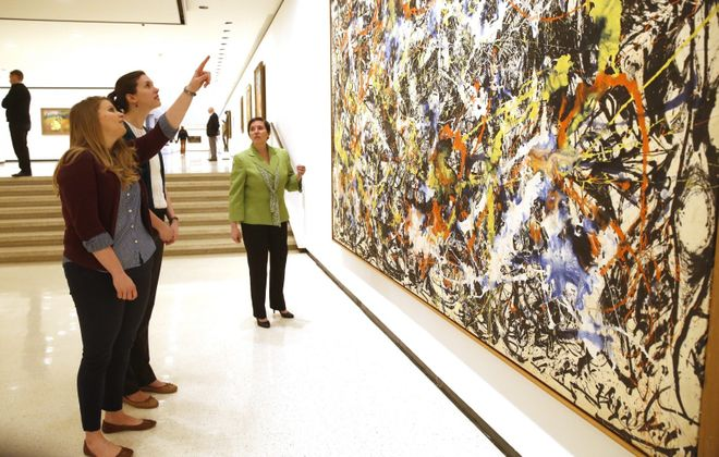 "From left, Kelly Macagnone, Elizabeth Bryson and community engagement director Jennifer Foley discuss Jackson Pollock's ""Convergence."""