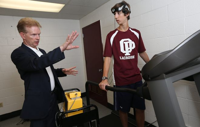 Dr. John Leddy Is a physician with UBMD Orthopaedics and Sports Medecine and Director of UB Concussion clinic.  He's working withJason Hanania, 14 from Orchard Park who is a volunteer for the healthy control group for a study using the treadmill to measure the severity of a concussion, Tuesday, July 7, 2015. It looks at the bloodflow during exercise using a doppler ultrasound device.  (Sharon Cantillon/Buffalo News)
