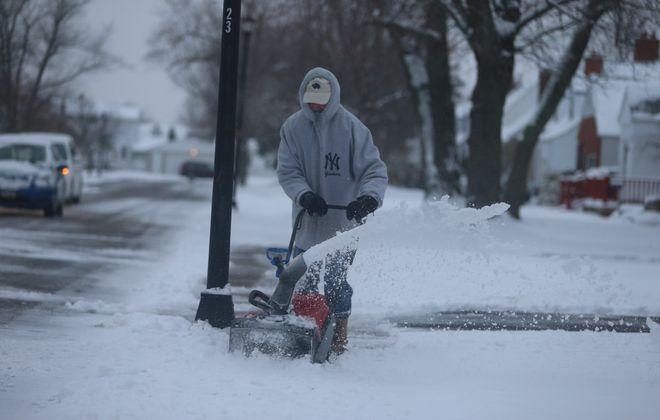 Jim Morrison snowblows his neighbor's sidewalks on Truesdale Road in the Town of Tonawanda Monday. (John Hickey/Buffalo News)