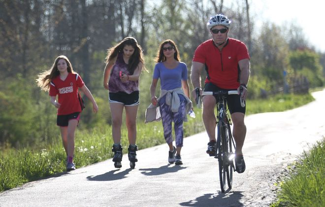 Dr. Marc Fineberg, right, shares part of the Clarence bike path with Ella Petrulla, 11, left, her friend Eva Nuchereno, 11, and her friend's mother, Norine Nuchereno. The bike path has been a popular way to get some exercise since the Covid-19 pandemic was announced last week, though social distancing of at least 6 feet is now common. Exercise is one of several ways to boost immunity. (Sharon Cantillon/News file photo)