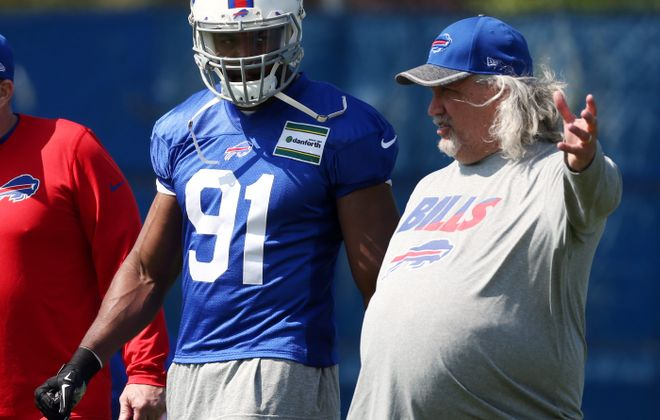 Bills assistant Rob Ryan gives instruction to outside linebacker Manny Lawson at Tuesday's workout at ADPRO Sports Training Center.