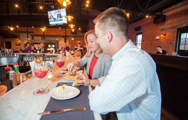 Sophia Chianese and Andrew MacKinnon, both of Buffalo, enjoy a bite at the bar at Remington Tavern in North Tonawanda. (Michael P. Majewski)