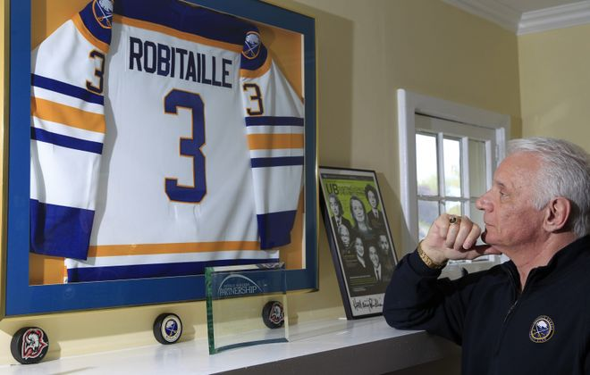 Mike Robitaille with a framed Sabres jersey that hangs in his home in 2016. (Harry Scull Jr./News file photo)