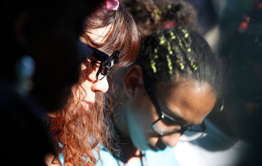 """The mother and sister of 11-year-old Juan """"Macho"""" Rodridguez bow their heads in prayer at a vigil held for the two shooting victims on Humason Avenue. (Sharon Cantillon/Buffalo News)"""