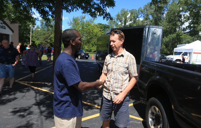 North Tonawanda firefighter Kenneth Walker, left, thanks Jim Warren, of Clarence, who donated furniture and other items at a fundraiser for Walker at Gratwick Hose #6 on Sunday, August 7, 2016. After Walker received a threatening letter, his home was burned. (John Hickey/Buffalo News)