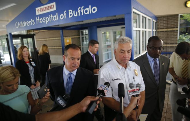 Buffalo Mayor Byron W. Brown, right, and Police Commissioner Daniel Derenda, center, hold a news conference Friday concerning the shooting of 8-year-old Donnell Bibbes on Thursday night.