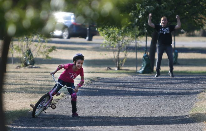Ivette Rivera celebrates as daughter Serenity, 8, successfully rides a two-wheeler for the first time. (Sharon Cantillon/Buffalo News)