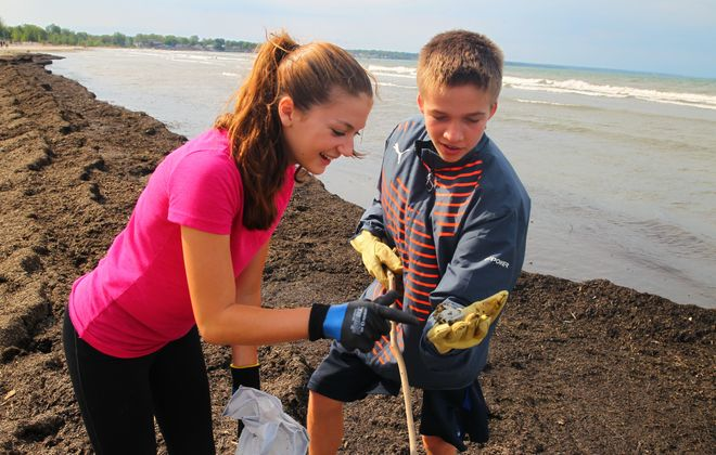 Madeline Venturo, 15, and Josh Valentine, 14, from Orchard Park Presbyterian Church inspect a piece of plastic – among thousands of items cleaned up by them and other volunteers – at Woodlawn Beach State Park during the 31st annual Great Lakes Beach Sweep.