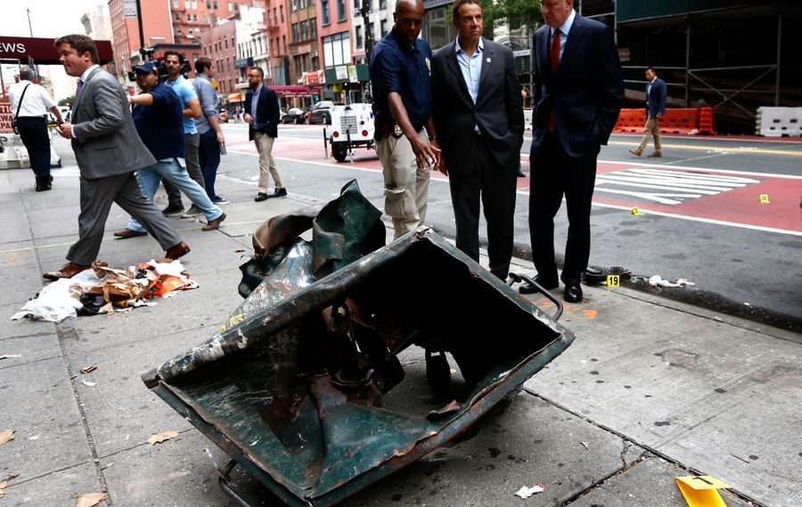 New York Mayor Bill de Blasio and New York Gov. Andrew Cuomo stand in front of a mangled dumpster while touring the site of an explosion that occurred Sept. 18 in the Chelsea neighborhood of New York City. (Justin Lane-Pool/Getty Images)