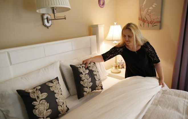 Salina Smouse makes up a bed in a guest room at the Butler House Bed and Breakfast in Niagara Falls. The Butler House takes a small percentage of its bookings from Airbnb. (Derek Gee/News file photo)