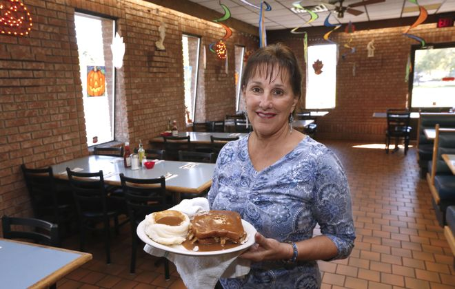 Head server Rose Matyjasik serves the open face fresh turkey sandwich, gravy and mashed potatoes at the  Seneca Towne restaurant.   (Robert Kirkham/Buffalo News)