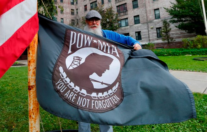 Paul DeFrain holds the POW MIA flag he flies in front of the appartment building he lives in on Elmwood in Buffalo. (Mark Mulville/Buffalo News)