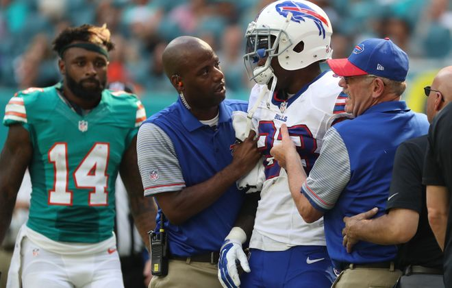 Bills safety Aaron Williams is attended to by trainers as Jarvis Landry looks on. (James P. McCoy/Buffalo News)