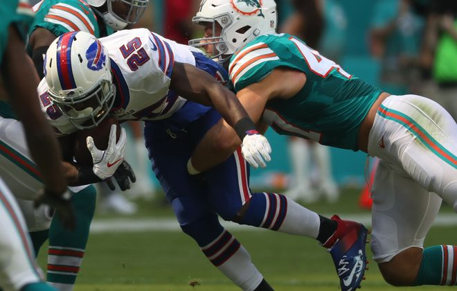 Buffalo Bills running back LeSean McCoy (25) is tackled by Miami Dolphins middle linebacker Kiko Alonso (47) in the second quarter.  (James P. McCoy/Buffalo News)