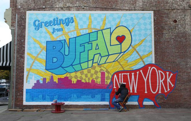 "Artist Casey William Milbrand is working on his colorful new ""Greeting from Buffalo"" mural on the south side of the Washington Market building at 461 Ellicott St. (Sharon Cantillon/Buffalo News)"