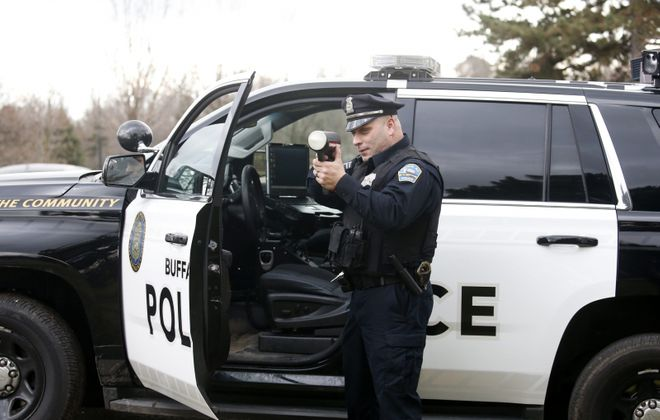 Buffalo Police Officer Obed Casillas aims a radar gun to catch speeders on Delaware Avenue in 2016. But some groups suspect traffic enforcement today is heaviest in the city's poorer neighborhoods. (Robert Kirkham/News file photo)