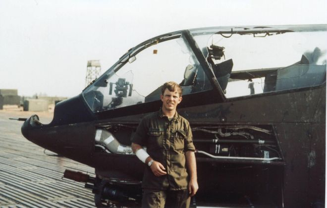 Army Warrant Officer 1 Jimmie D. Ferguson stands in front of a Cobra attack helicopter on Jan. 20, 1972, at a base in Phu Bai, Vietnam. Ferguson was shot down while flying it a day earlier, and suffered an accidental stab wound from the aircraft commander while they were escaping (note the arm bandage). (Photo courtesy of Jimmie D. Ferguson)