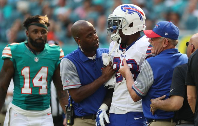 Buffalo Bills strong safety Aaron Williams (23) gets helped off the field after being hurt in the second quarter at Hard Rock Stadium on Oct. 23, 2016.  Miami player Jarvis Landry, who hit Williams with an illegal crackback block, looks on. (James P. McCoy/Buffalo News)