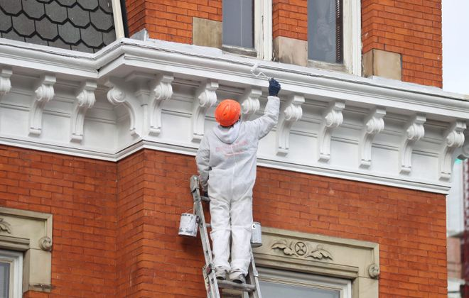 A crew member from Darling Paint works on trim on the August Feine House, the newest component of the Kevin Guest House and the site of the 2017 Decorators' Show House running April 29 through May 21, 2017. (John Hickey/Buffalo News)