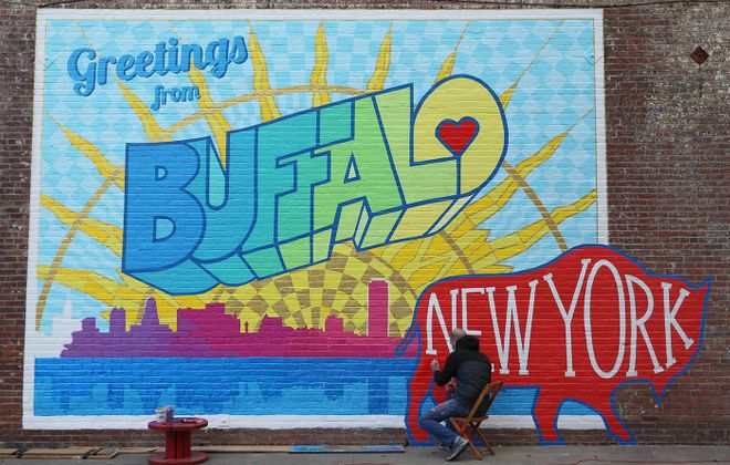 """Artist Casey William Milbrand works on his colorful new """"Greetings from Buffalo"""" mural on the south side of the Washington Market building at 461 Ellicott St,, Tuesday, Oct. 25, 2016.  (Sharon Cantillon/Buffalo News)"""