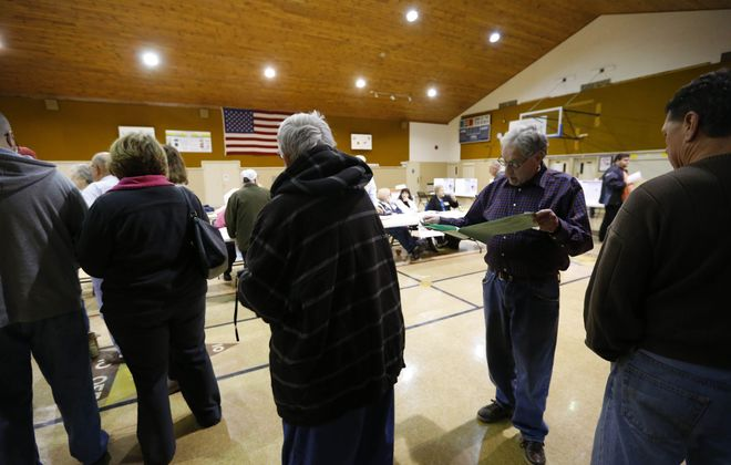 Election worker Jimmy Zawadzki helps voters in line at 14 Holy Helpers Church in West Seneca Tuesday.   (Mark Mulville/Buffalo News)
